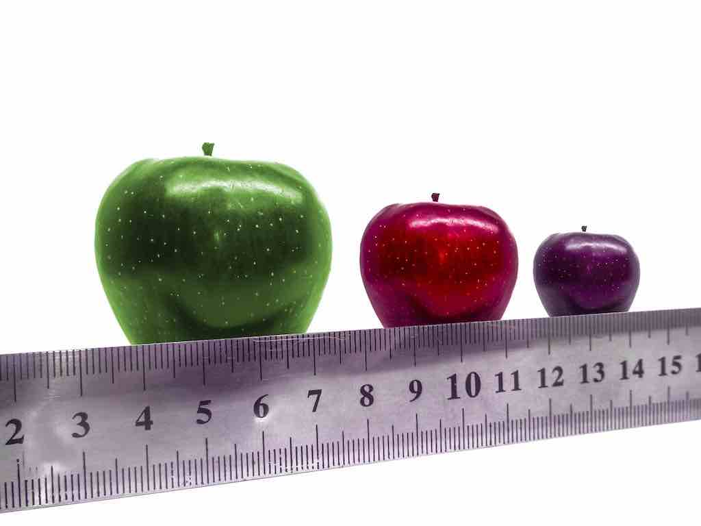Three apples of different sizes and colors