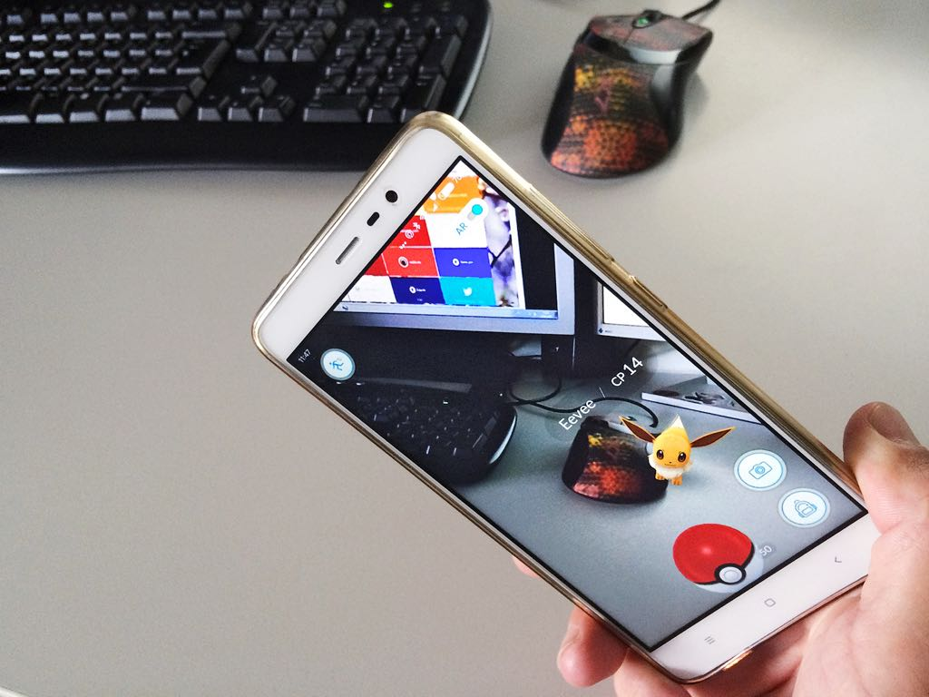 Pokémon Go being played over a desk with a pokémon being superimposed using AR.