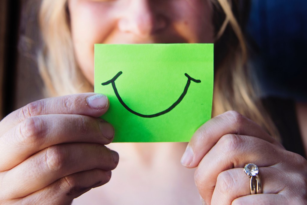 Woman with post-it with smile