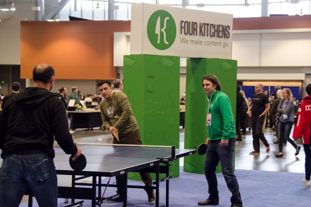 Four Kitchens at Drupalcon showing off their latest repositioning tool, a ping-pong table!